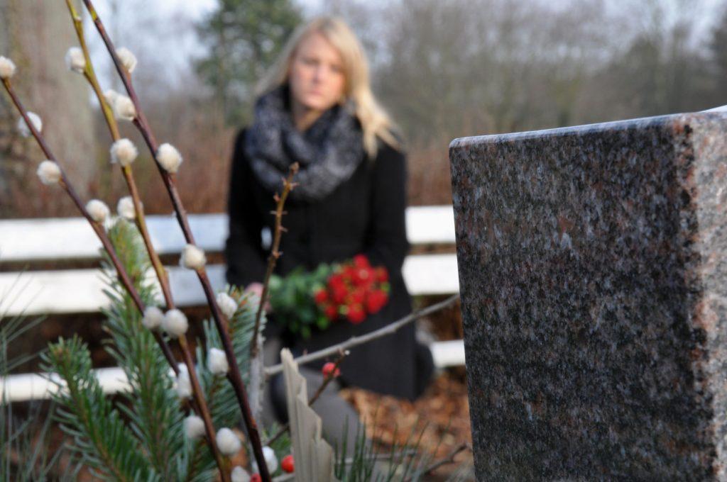 Frau trauert an Grab