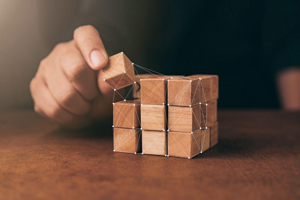 Mann baut Würfel aus einzelnen Bausteinen.