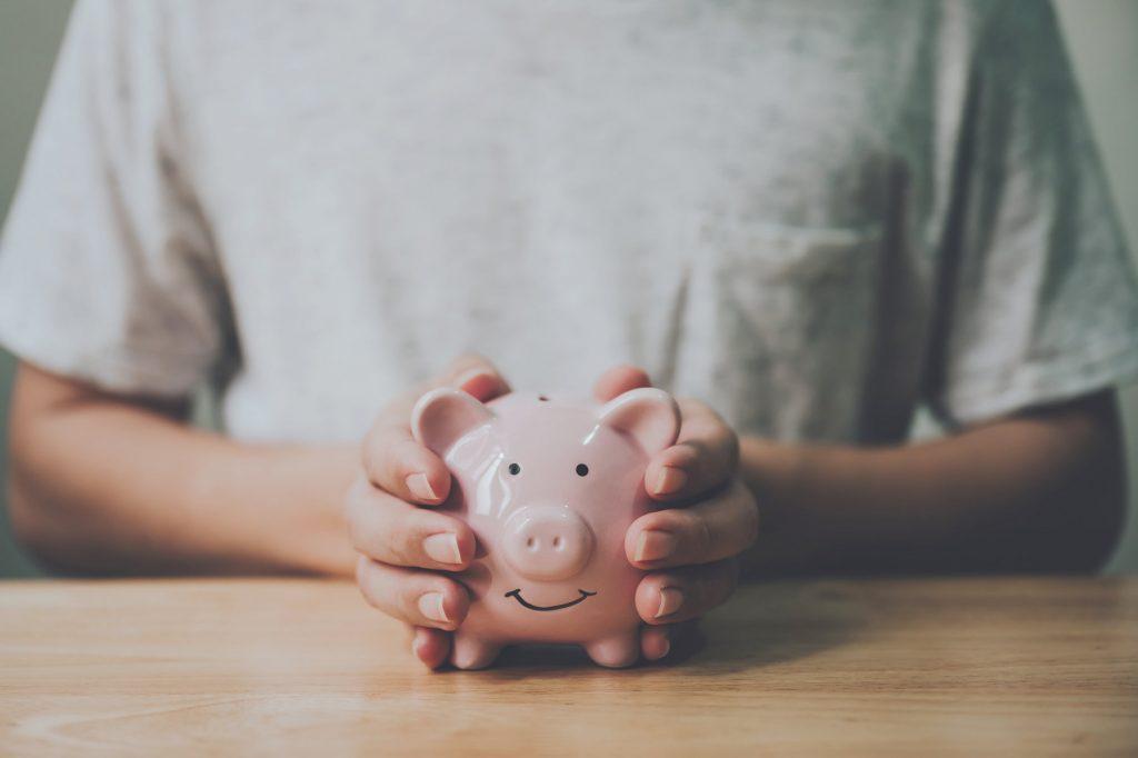 Mann hält Sparschwein mit beiden Händen