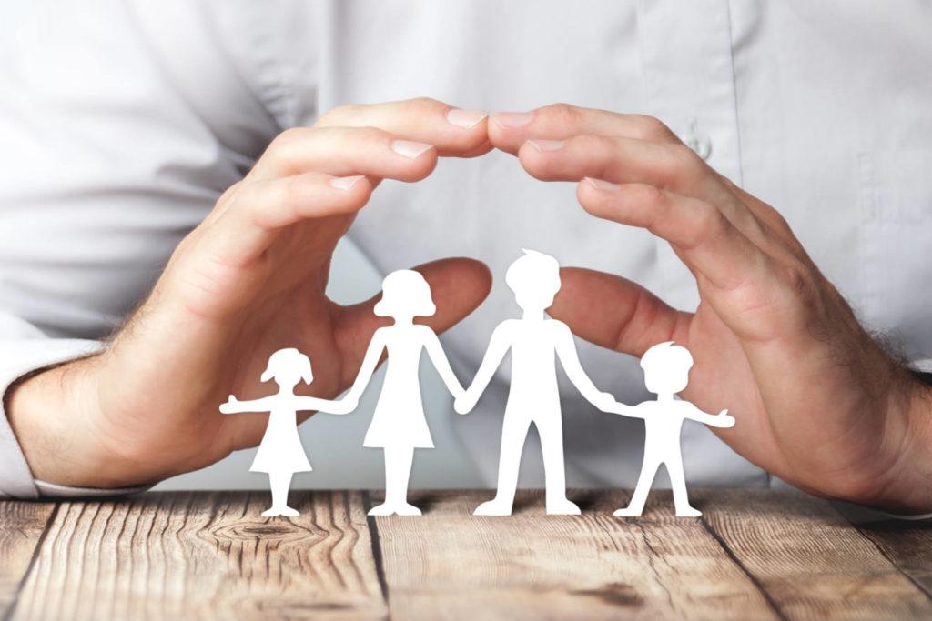 Hände schützen über Familie aus Papier